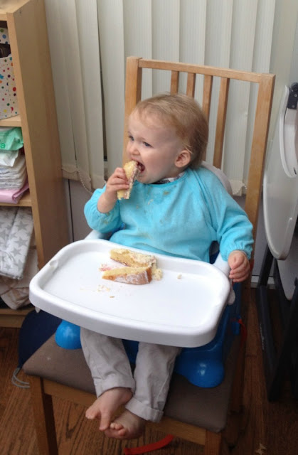 baby eating cake sat in high chair