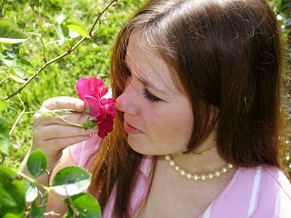 A lady smelling a flower and appreciating simple things.