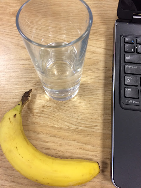 A glass of water and a banana next to a laptop
