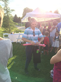 A Balloon Artist making a balloon animal for a crowd of custumers