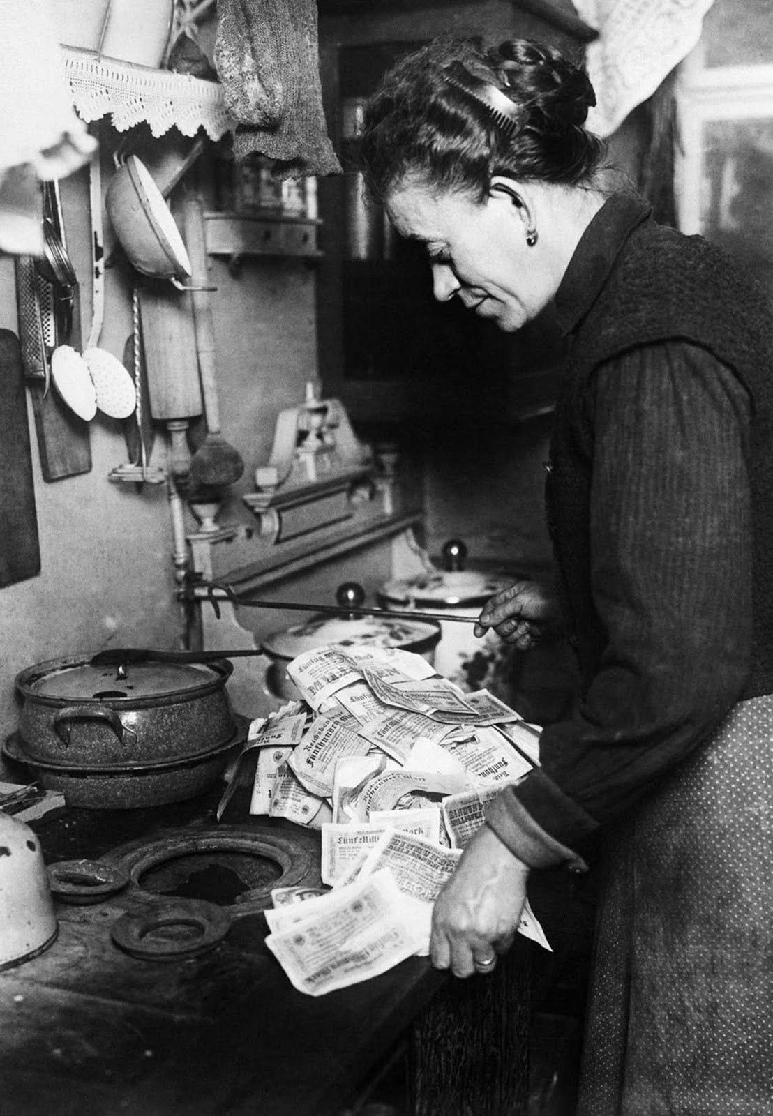 A woman uses banknotes to light her stove. 1923.
