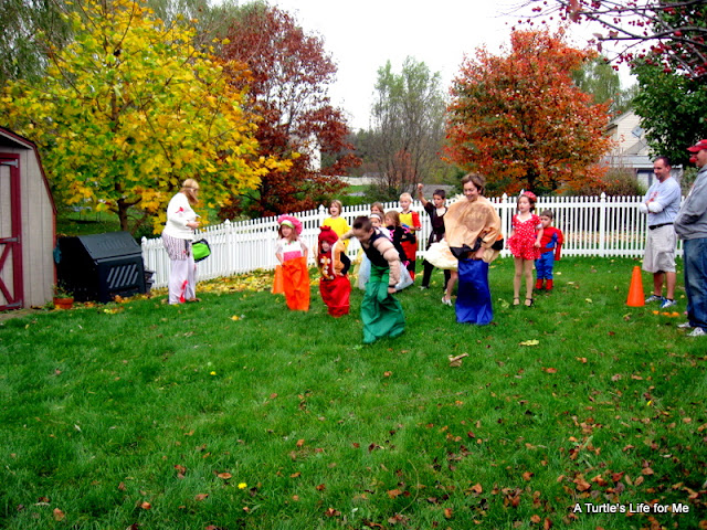 Kids participating in a backyard potato sack race while in Halloween costumes