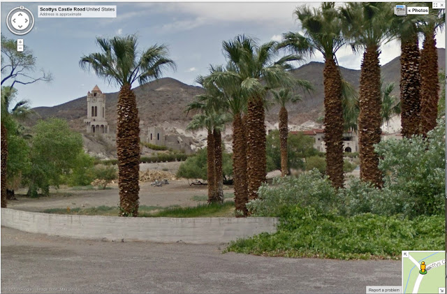 oasis in the arid desert with palm trees surrounding a castle