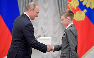 Vladimir Putin presents passports to young citizens of Russia.