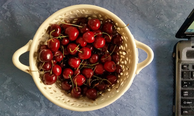 Above view of a bowl of red cherries (centre) and the corner of a black laptop computer (right hand side). They are resting on a tabletop covered with a mid-blue tablecloth. The bowl is off-white ceramic with two handles and cast in a filigree lace pattern.