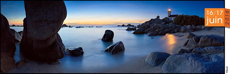 Photo panoramique en couleur d'un bord de mer avec des rochers à la tombée du jour.