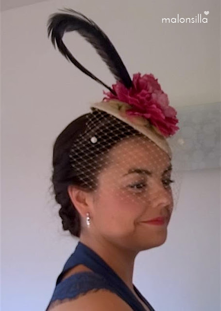 Invitada boda de perfil con vestido azul petróleo y tocado fucsia, crudo y azul con velo, flores y pluma