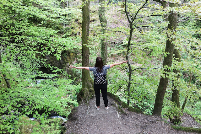 I'm wearing black dungarees and standing in front of a forest and waterfall with my arms outstretched