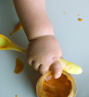 Baby's hand with jar of food