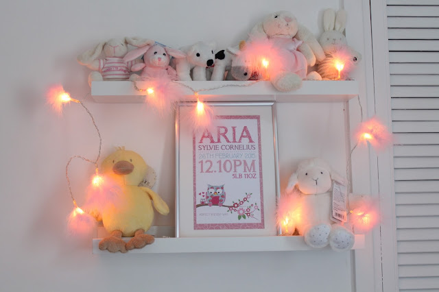 ikea ribba shelving in baby room with pink fairy lights to store teddy bears