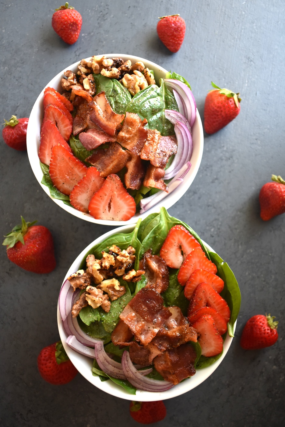 Strawberry Spinach Salad with Warm Bacon Vinaigrette is the perfect salad with red onions, strawberries, crispy bacon, toasted nuts and a warm bacon dressing! www.nutritionistreviews.com