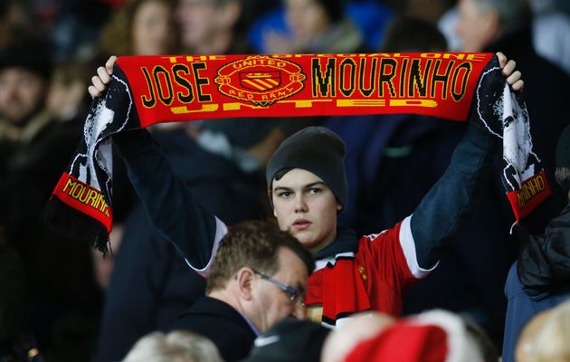 Manchester United fan displays a scarf in reference to former Chelsea manager Jose Mourinho. Image by: Phil Noble / REUTERS