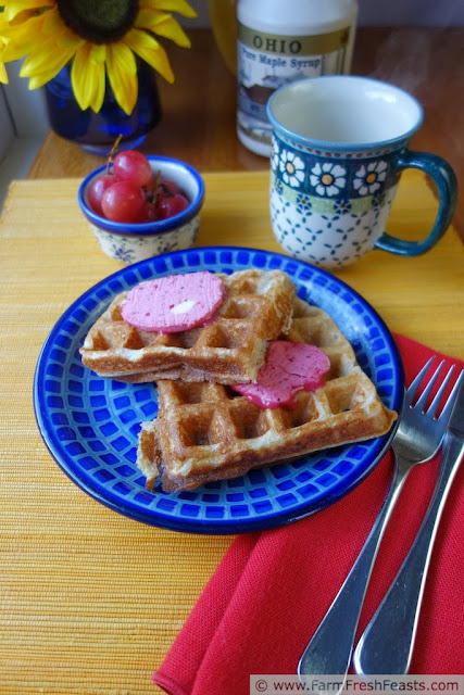 image of a plate of waffles topped with cranberry honey butter, served with a side of grapes and a jug of maple syrup