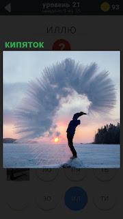 Мужчина зимой на поле кипятком в воздухе образовал узор из воды