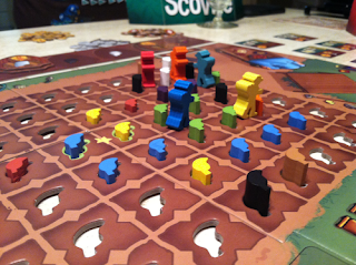 The board in the middle of a game. The focus of this photo is the central area of the board, a plot of farmland represented by several brown squares in a grid. Each square has a cutout in the shape of a chili pepper. Some of these have wooden pepper-shaped tokens in various colours in them. There are five farmer-shaped meeples in the board, standing between two squares on the board.