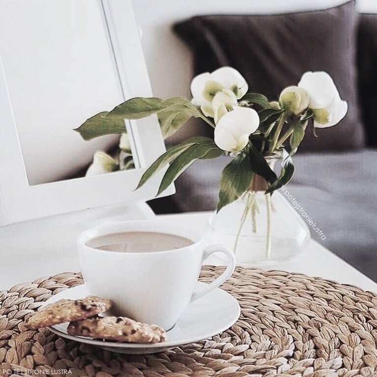 filiżanka kawy, owsiane ciasteczka i bukiet białych piwonii na toaletce