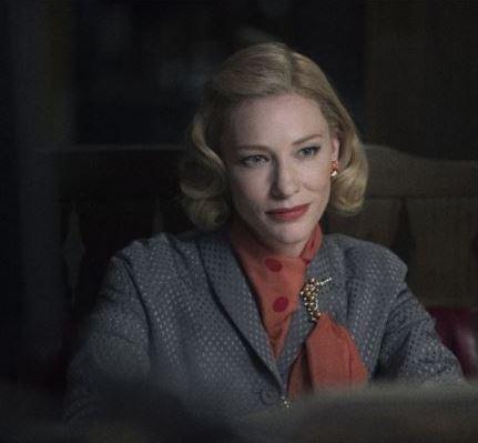 Carol com casaco cinza e broche de perolas na lapela, ela esta sentada