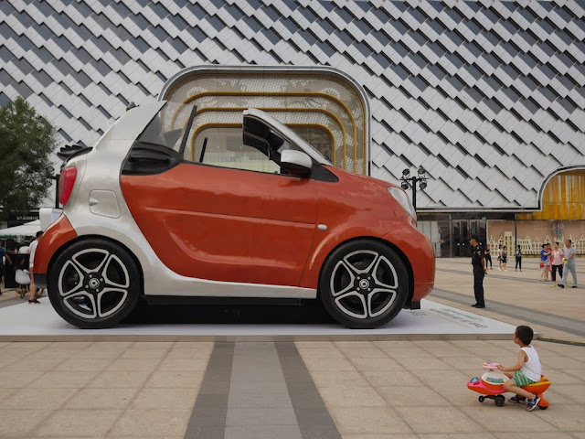 boy sitting on small toy vehicle looking at a giant version of a Smart car in Taiyuan
