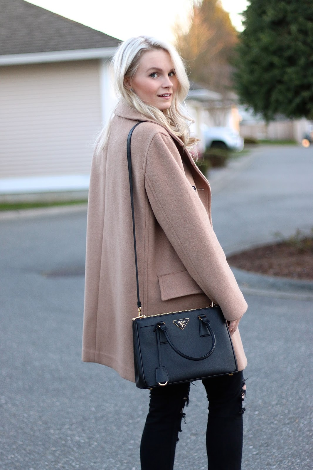 blonde blogger wearing fall style clothing and prada handbag