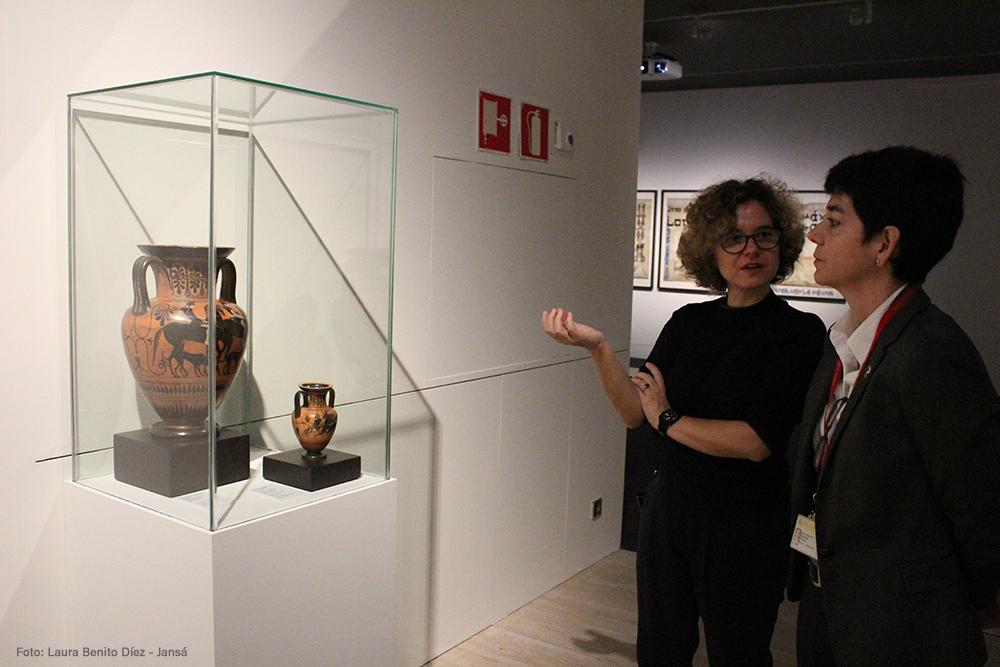 Clara Carvajal y la conservadora Marga Moreno dialogan frente a dos piezas de cerámica griega con representaciones de amazonas