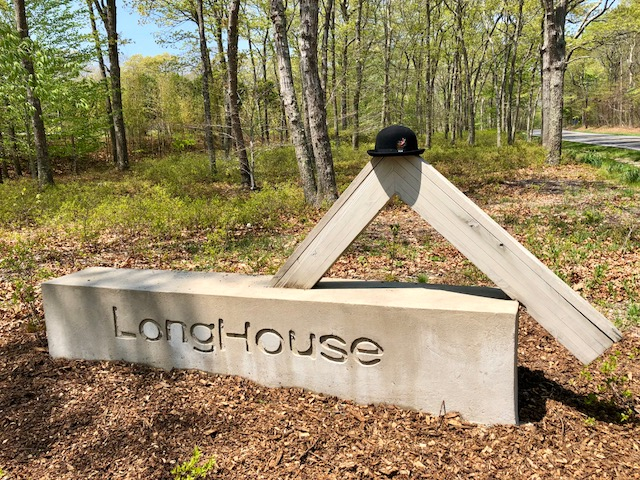 concrete sign for LongHouse Gardens, with a bowler hat perched atop it