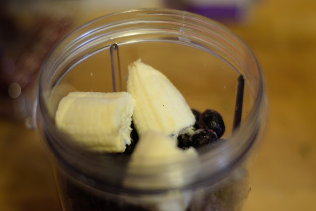 Banana and blueberries being added to the blender.