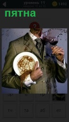 Мужчина в пиджаке и тарелкой от которой пятна на всей поверхности одежды