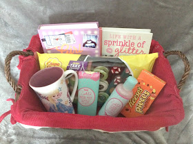 gift basket filled with toiletries, sweets, book, mug