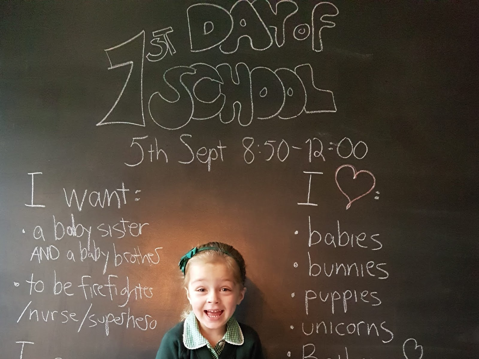 kid in front of blackboard with first day of school written on it