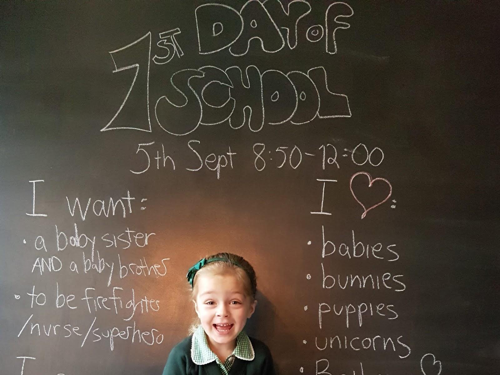 kid in front of blackboard with first day of school written on it