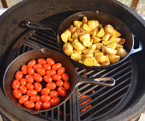 Lodge cast iron skillets on a Big Green Egg kamado grill making some grilling sides.
