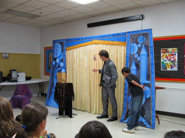 A magic show in progress with a boy volunteering
