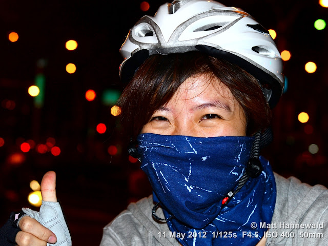 people, street portrait, headshot, face, eyes, Taiwan, Taipei, face bandana, cyclist, bicycle helmet, thumbs-up sign, eye contact
