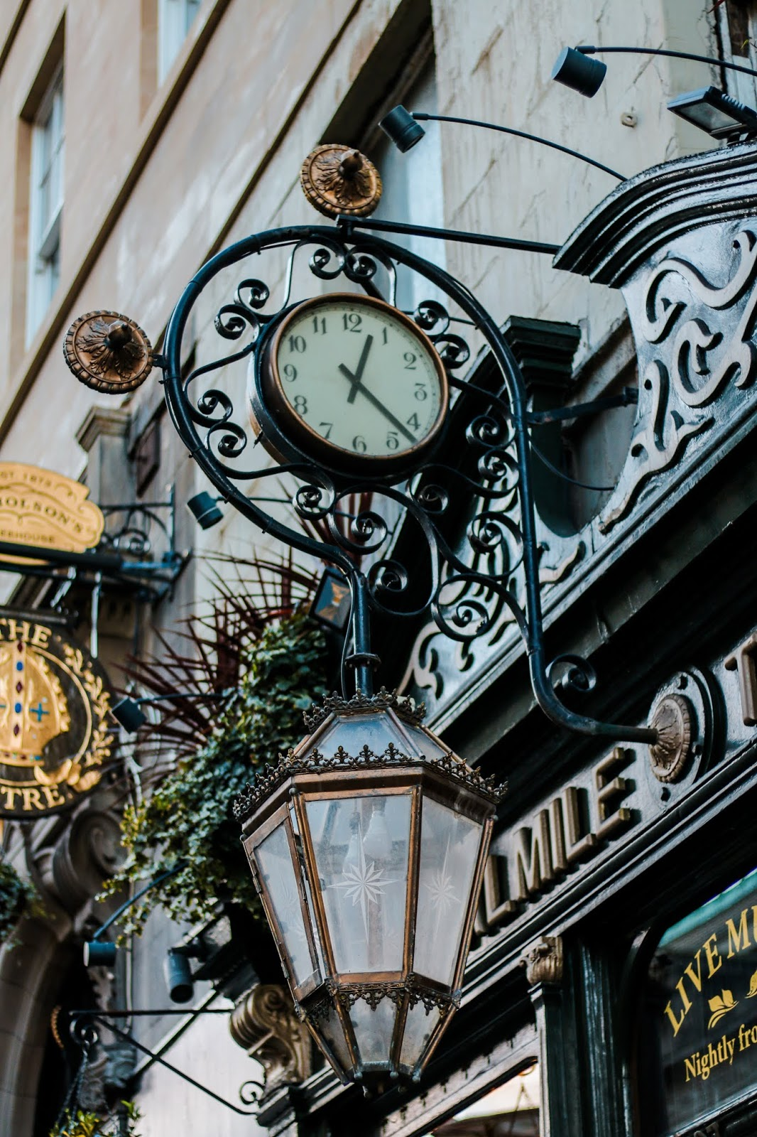 close up photo of a hanging clock outside of the royal mile tavern in Edinburgh