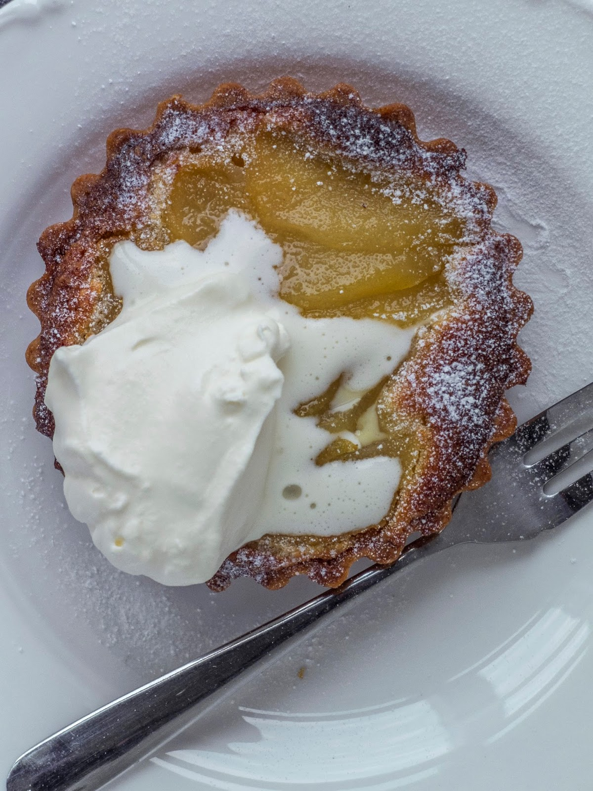 A closeup image of a sweet pastry pear tart with a dollop of cream on top.