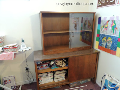 empty glass hutch with magazines in storage beneath
