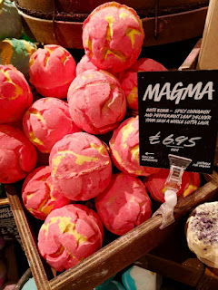 A selection of bright red spherical bath bombs with yellow crack patterns all over on a wide light brown rectangular shelf with a black board saying magma on white font on a bright background