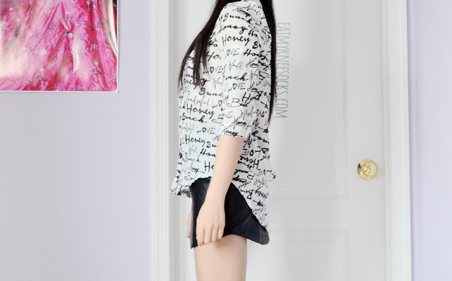 A sleek, modern, edgy outfit featuring a three-quarter sleeve semi-sheer graffiti word print graphic button-down high-low blouse and faux leather skirt from Dresslink.