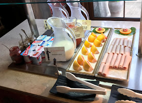some breakfast items of grapefruit, meat, yogurts and drinks