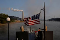 The U.S. flag flies on a towboat as it passes a coal-fired power-plant along the Ohio River in Stratton, Ohio, U.S., September 10, 2017. (File Photo Credit: Reuters/Brian Snyder) Click to Enlarge.