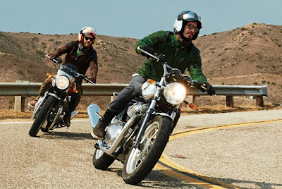 Two motorcycle riders lean into a turn.