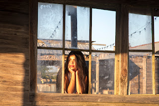 A girl peeks out a window frame in the J Lorraine Ghost Town of Manor, Texas