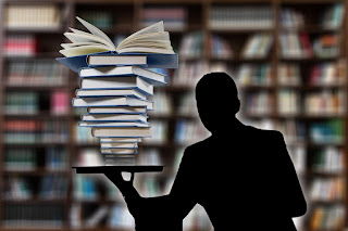 Silhouette of person balancing stack of books on top of a single laptop computer