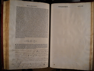 An open book. The lefthand page is filled with printed text and handwritten notes. The righthand page is blank.