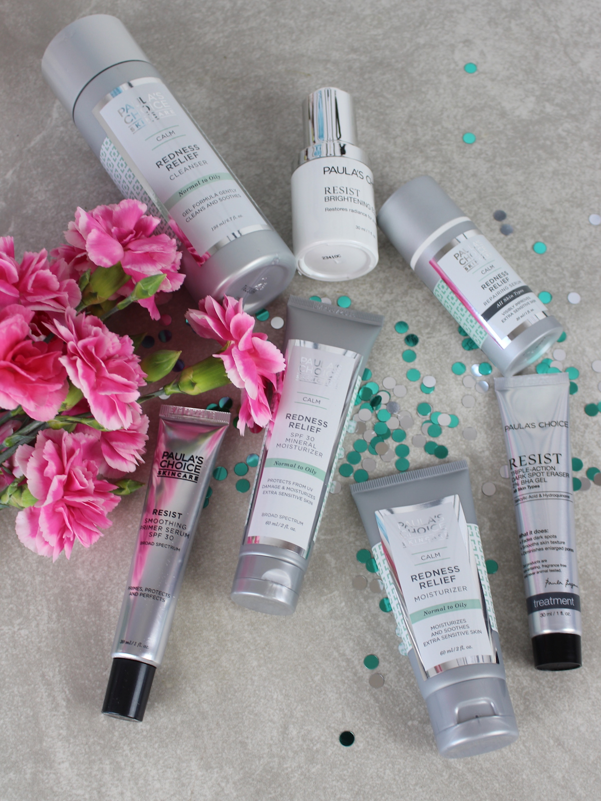 This is a close up of Paula's Choice skin care products for redness and dark spots, surrounded by beautiful pink flowers.