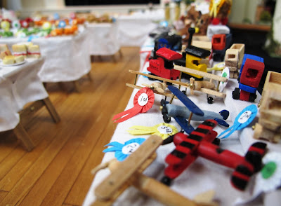 Wooden toys with prize ribbons on a stall in a one-twelfth scale scene of a CWI wartime fundraising fete in a hall.