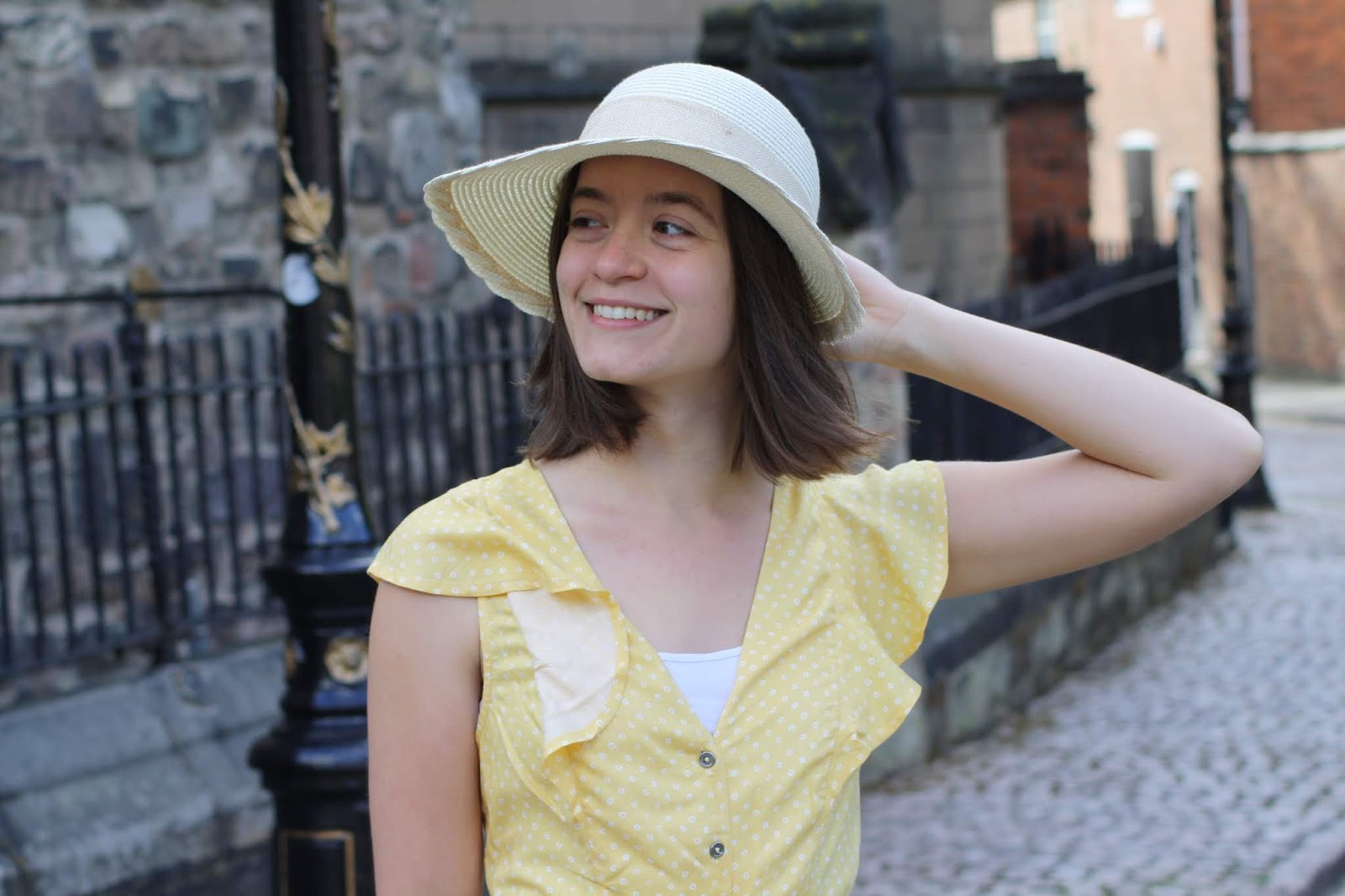 Abbey, wearing a yellow floaty dress, looks off to the left and touches the brim of her straw hat