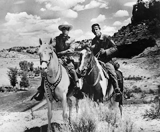 Scene from the Lone Ranger with Lone Ranger riding his horse Silver and Tonto riding Scout