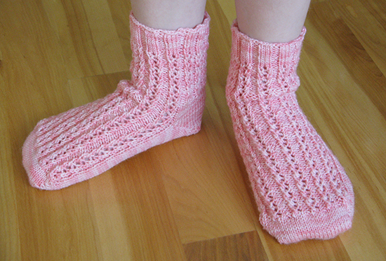 Pink Hand Knit Lace Socks on the Feet of a Child