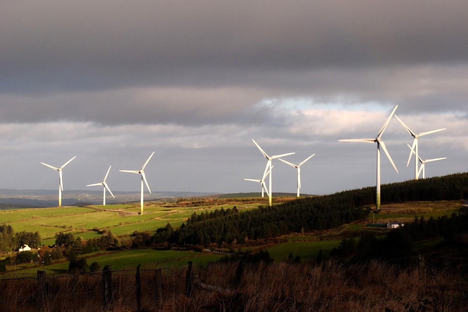 A dramatic Irish mountain landscape with a wind turbine farm.